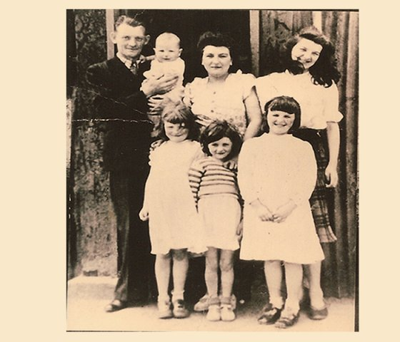 From left to right back row:  Eddie Kelly,[baby in arms Paddy Kelly]Bridget Kelly,Katie Kelly front row from left to right:  Maggie Kelly ,Georgina Kelly,Bernadette Kelly